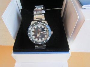 Đồng hồ Seiko 5 Automatic niềng nhái xanh chữ trắng, mặt xanh tia vô cùng nổi bật.