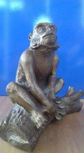 Chú khỉ ngồi trên góc cay bằng đồng